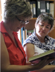 Figure 11.  Deani Van Pelt and Lisa Cadora looking through one of the books in Mason's personal book collection.